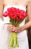 拿着红色郁金香花束的新娘 免版税库存照片