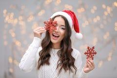 拿着红色雪花的圣诞节帽子的年轻美丽的夫人 免版税库存照片