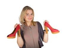拿着红色鞋子的年轻可爱的妇女 免版税库存照片