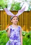 拿着红萝卜的兔宝宝耳朵的女孩 库存照片
