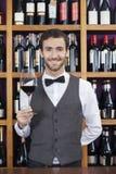 拿着红葡萄酒的侍酒者玻璃反对架子 免版税图库摄影