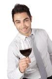 拿着红葡萄酒的商人玻璃 免版税库存图片