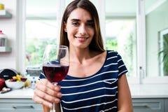 拿着红葡萄酒的微笑的少妇画象玻璃 库存照片