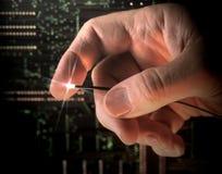 拿着纤维光学导线的手 免版税图库摄影
