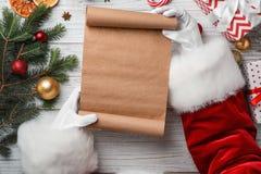 拿着纸卷和圣诞节装饰的圣诞老人 库存图片