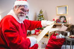 拿着纸卷的圣诞老人在客厅 免版税库存照片