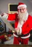 拿着纸卷的圣诞老人在客厅 库存图片