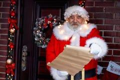 拿着纸卷纸的微笑的圣诞老人 免版税库存图片