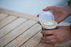 拿着纸咖啡杯的女性手 库存图片