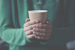 拿着纸咖啡的手 免版税库存照片
