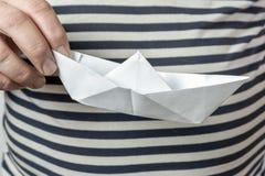 拿着纸小船的一件镶边背心的一个人 海和河旅行,航海的概念 免版税库存照片