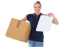 拿着纸板箱和剪贴板的愉快的交付妇女 免版税库存照片