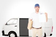 拿着纸板箱和剪贴板的愉快的送货人的综合图象 免版税库存图片