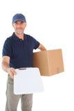 拿着纸板箱和剪贴板的愉快的送货人 库存照片