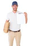 拿着纸板箱和剪贴板的愉快的送货人 免版税图库摄影