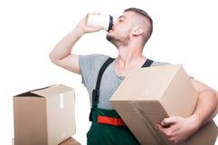 拿着纸板箱和喝咖啡的搬家工人人 库存图片