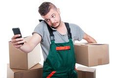 拿着纸板箱和浏览智能手机的搬家工人人 库存照片