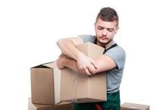 拿着纸板箱和他的手肘的搬家工人人 免版税图库摄影