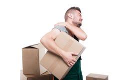 拿着纸板箱和他的肩膀的搬家工人人 库存图片