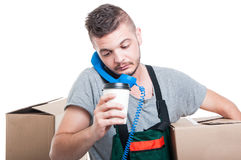 拿着纸板箱咖啡和电话的繁忙的搬家工人人 免版税库存图片