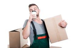拿着纸板箱的搬家工人人享用咖啡 免版税库存图片