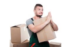 拿着纸板箱的搬家工人人打手势祷告 库存照片