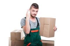 拿着纸板箱的搬家工人人显示手指横渡 免版税库存照片
