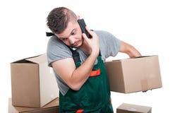 拿着纸板箱的搬家工人人谈话在电话 免版税库存照片