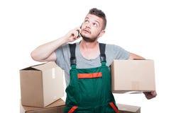 拿着纸板箱的搬家工人人谈话在电话 库存照片