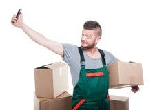 拿着纸板箱的搬家工人人采取selfie 免版税图库摄影