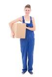 拿着纸板箱的蓝色工作服的年轻可爱的妇女是 免版税库存图片