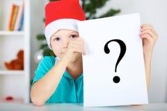 拿着纸片与问号标志的圣诞老人红色帽子的滑稽的男孩 圣诞节概念 免版税图库摄影
