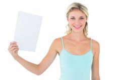 拿着纸片的愉快的金发碧眼的女人 免版税库存图片