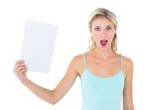 拿着纸片的震惊金发碧眼的女人 免版税库存图片