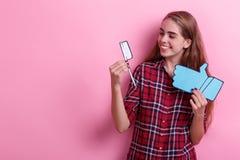 拿着纸牙刷和赞许的标志和看它的女孩 在桃红色背景 库存照片