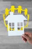 拿着纸的手的综合图象一个房子 免版税图库摄影