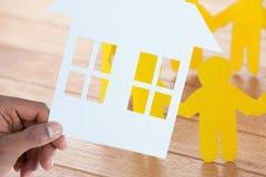 拿着纸的手的综合图象一个房子 库存照片