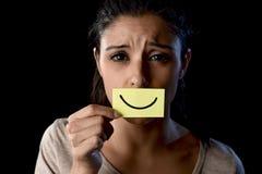 拿着纸的拉丁哀伤的沮丧的拉丁女孩掩藏她的在伪造品被画的微笑后的嘴 免版税库存图片