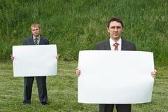 拿着纸页的生意人 免版税库存图片