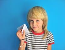 拿着纸飞机的快乐的白肤金发的男孩画象  库存照片