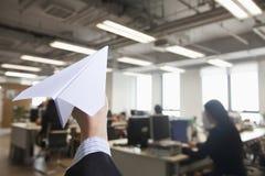 拿着纸飞机的手在办公室 免版税库存照片
