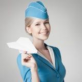 拿着纸飞机的迷人的空中小姐手中。灰色背景 库存照片