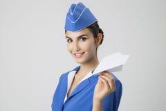 拿着纸飞机的迷人的空中小姐手中 灰色背景 库存照片