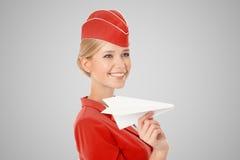 拿着纸飞机的迷人的空中小姐手中 灰色背景 免版税库存照片