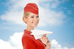 拿着纸飞机的迷人的空中小姐手中 库存图片