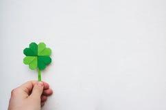 拿着纸origami绿色三叶草的手 图库摄影