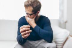 拿着结婚戒指的极悲痛的人 免版税库存照片