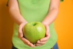 拿着绿色苹果在手上的少妇上色背景 库存图片