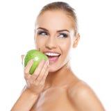 拿着绿色苹果的微笑的秀丽 库存照片