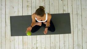 拿着绿色苹果,密林的可爱的妇女用它,坐锻炼席子 免版税库存图片